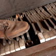 Stock Photo: Old Dirty Piano With Old Leather Shoe