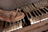 Old Dirty Piano With Old Leather Shoe — Stock Photo