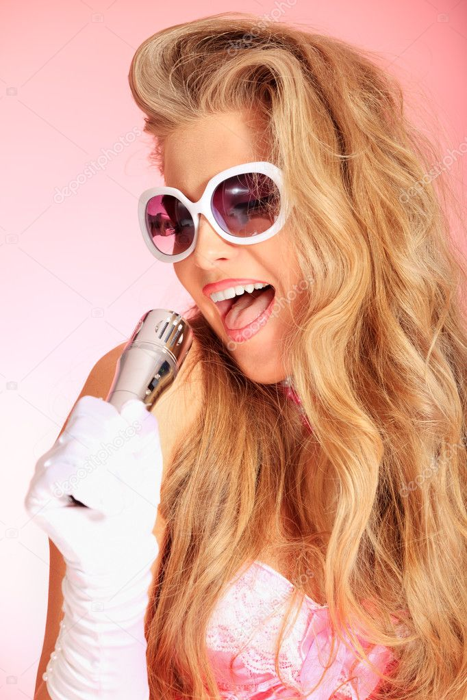 Portrait of a charming blonde woman singing with microphone in studio over pink background. — Stock Photo #10768548
