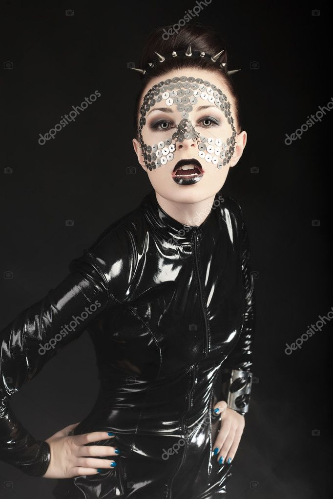 Conceptual shot of a woman in black glossy overall and metal buttons on her face. — Stock Photo #10768621