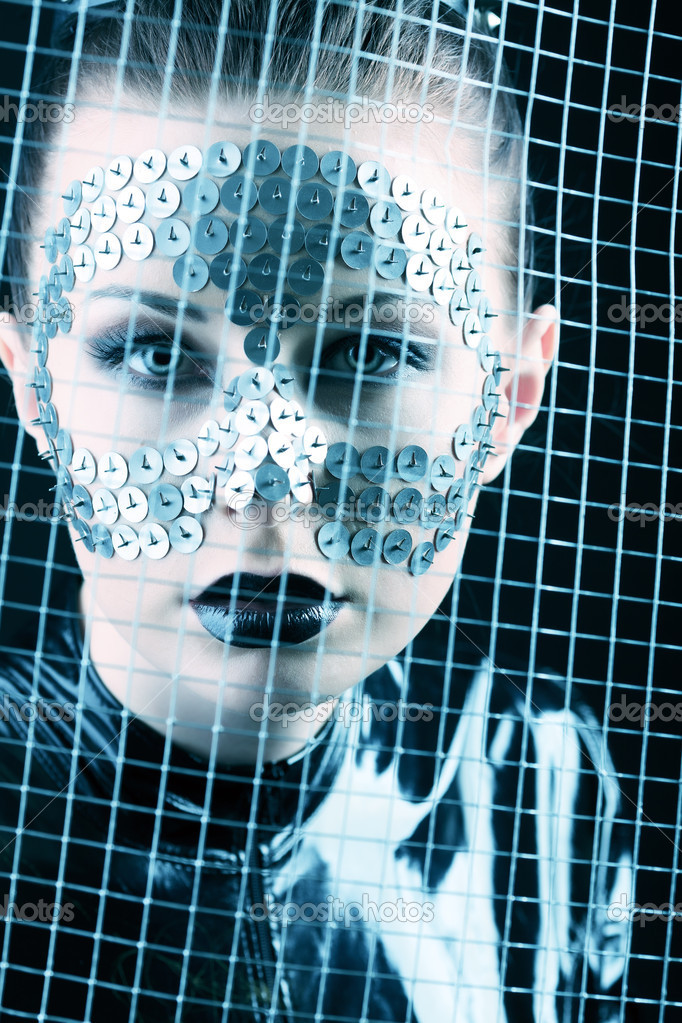 Conceptual shot of a woman in black glossy overall and metal buttons on her face. — Stock Photo #10768632