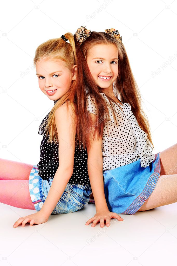 Portrait of two little girls sisters posing at studio.