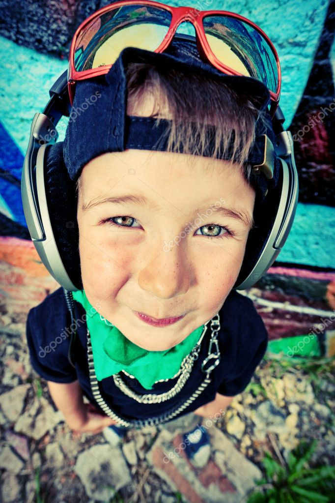Portrait of a trendy little boy  with headphones outdoors. — Stock Photo #10952278