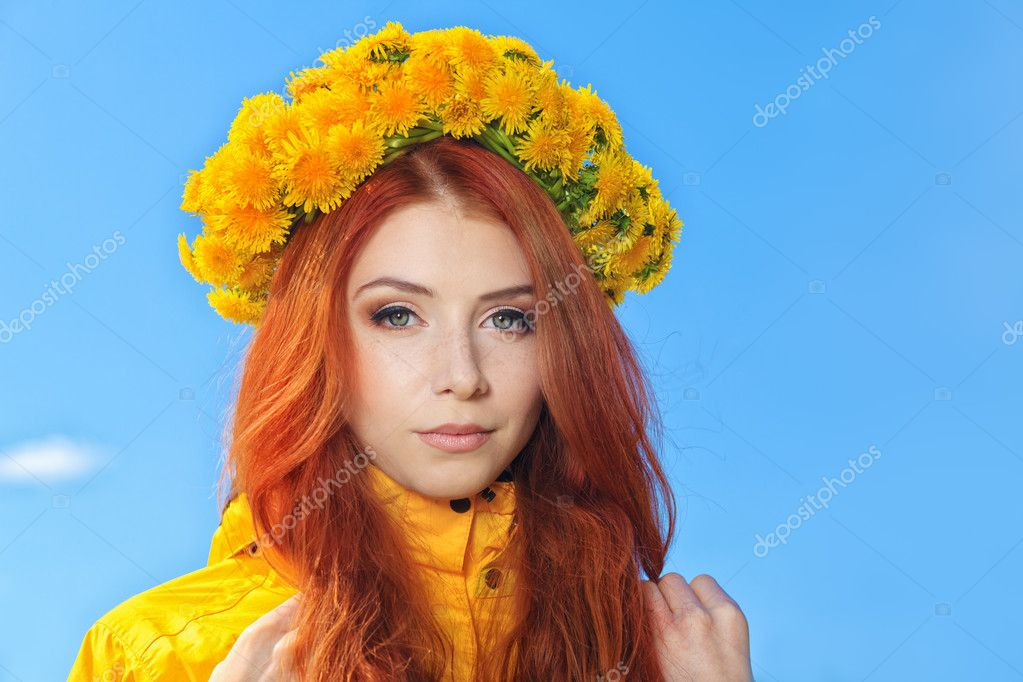 Beautiful young woman in a circlet of flowers over blue sky. — Stock Photo #10952576