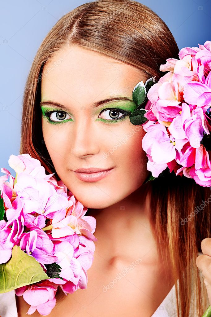 Portrait of a beautiful tanned woman posing with flowers. — Stock Photo #10972958
