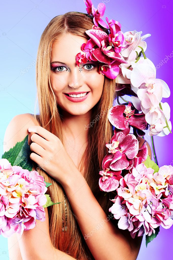 Portrait of a beautiful tanned woman posing with flowers. — Stock Photo #10972971