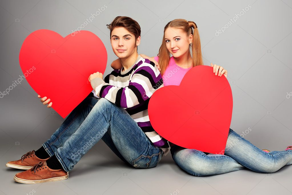 Happy young love couple posing together with red hearts.  Stock Photo #10973039