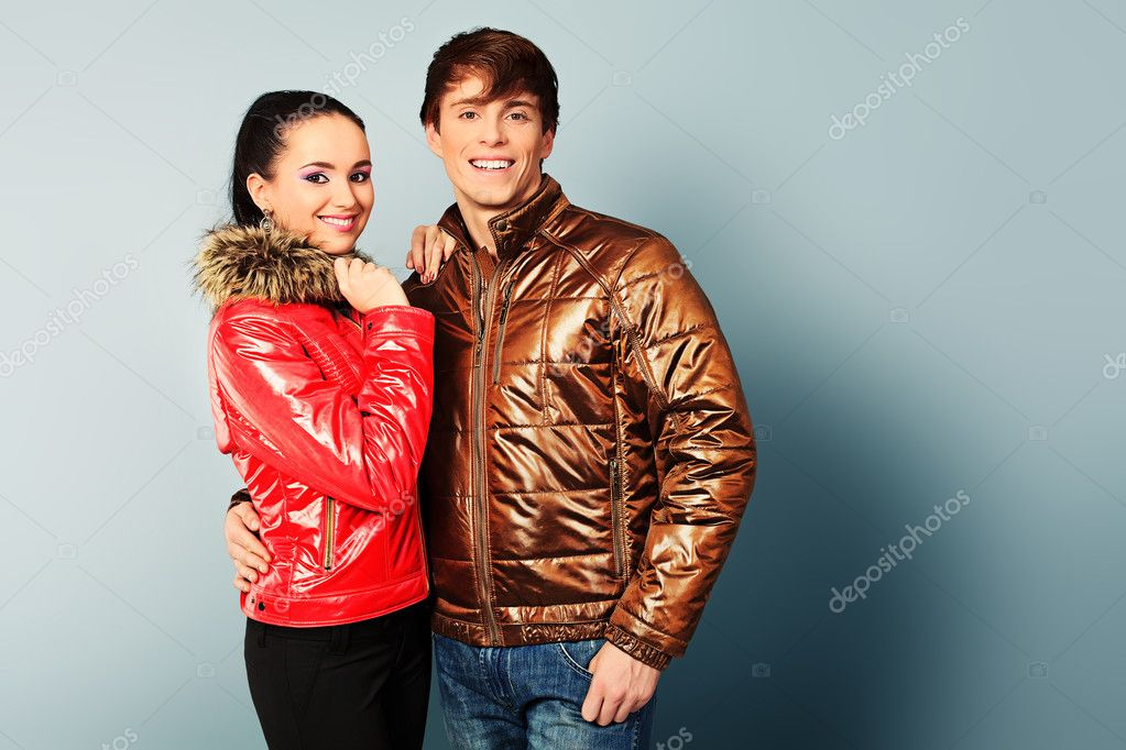 Couple of fashion models in winter, spring clothes posing at the studio. — Stock Photo #10995856