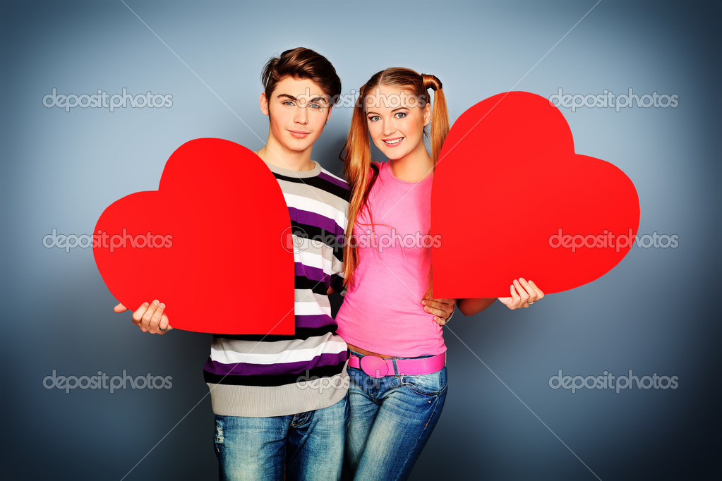 Happy young love couple posing together with red hearts.  Stock Photo #10995901