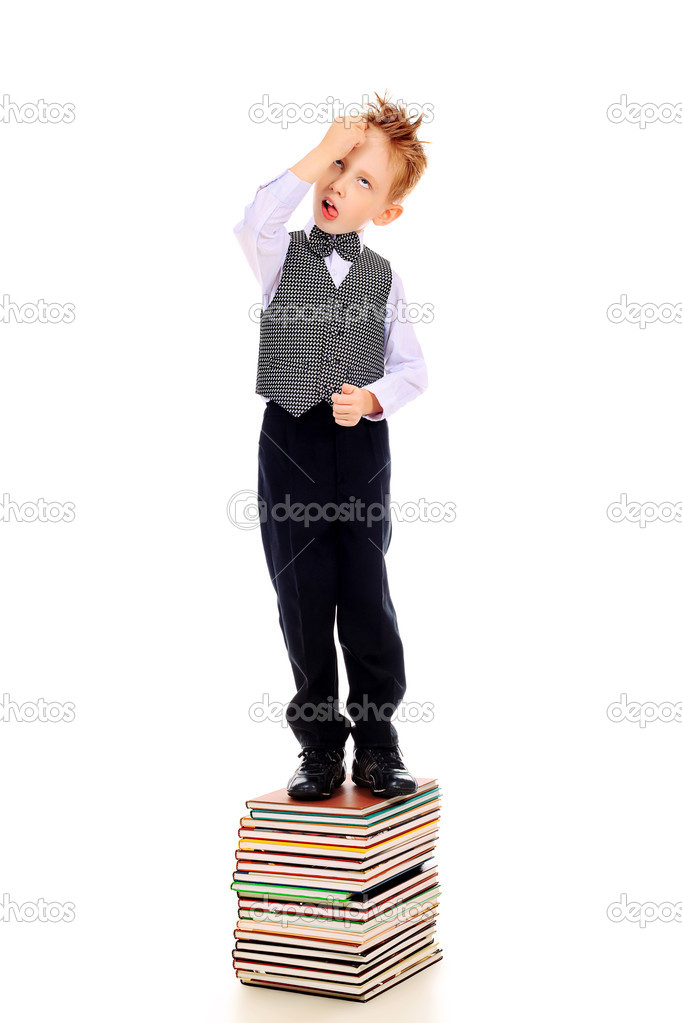 Portrait of a little boy standing on a stack of books. Isolated over white background.  Stock Photo #10996099