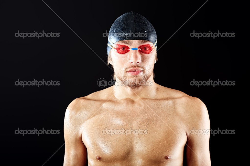 Portrait of a man professional  swimmer posing at studio over black background. — Stock Photo #11013560