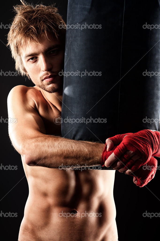 Portrait of a handsome boxer in red gloves posing at studio. — Stock Photo #11013569