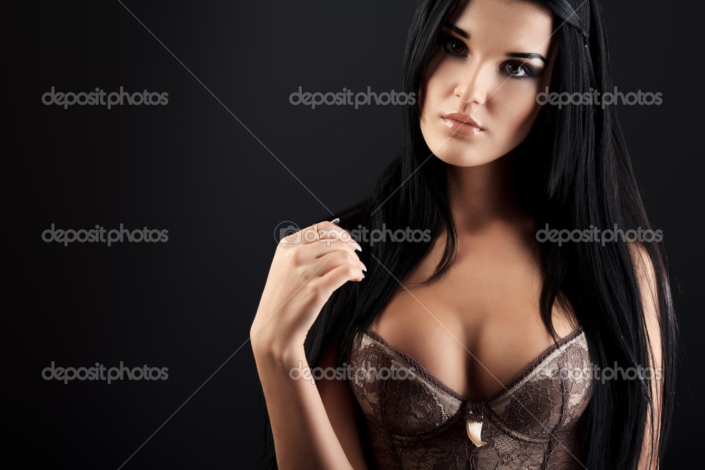 Shot of an attractive young woman in sexual lingerie, over black background. — Stock Photo #11144468