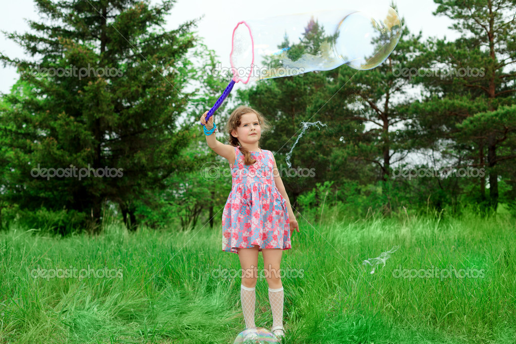 Happy girl is playing with big bubbles in a park.  Zdjcie stockowe #11288432