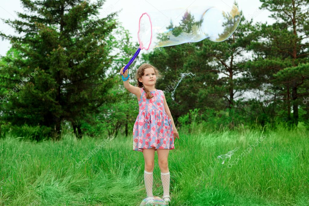 Happy girl is playing with big bubbles in a park. — Photo #11288432