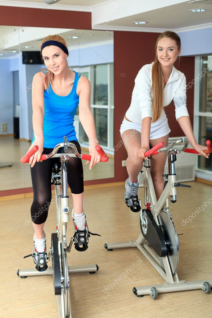 Young sporty women doing exercises on bicycles in the gym centre. — Stock Photo #11392329