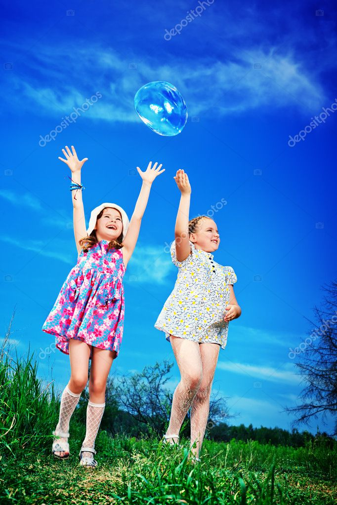 Two happy girls playing with big bubbles in a park. — Stock Photo #11509619