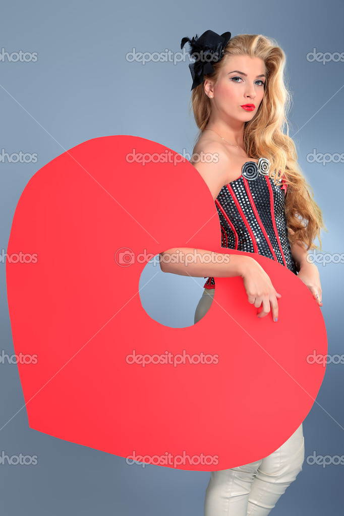 Beautiful young woman with pin-up make-up and hairstyle posing in studio with red heart. — Stock Photo #11686617