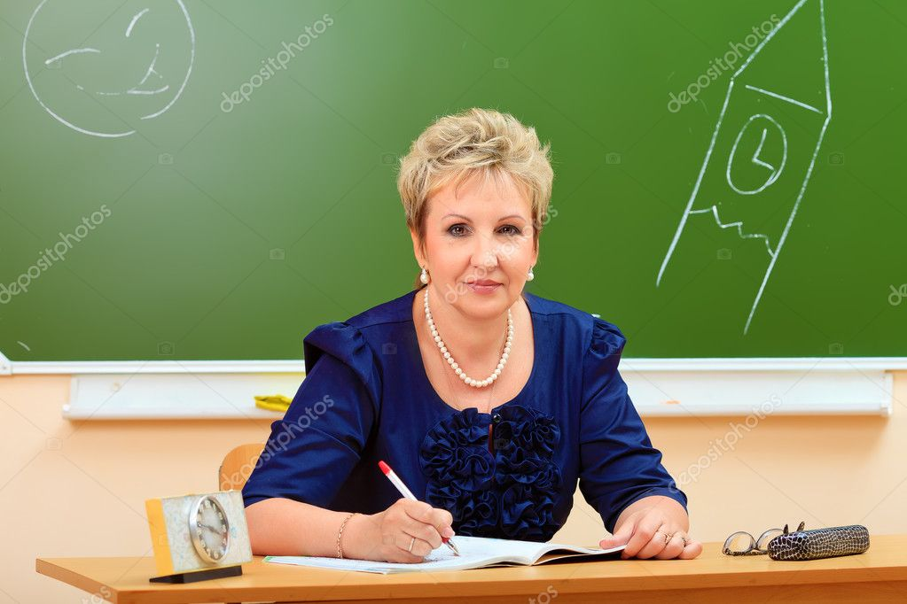 Portrait of a smiling teacher in a classroom. — Stock Photo #11686731