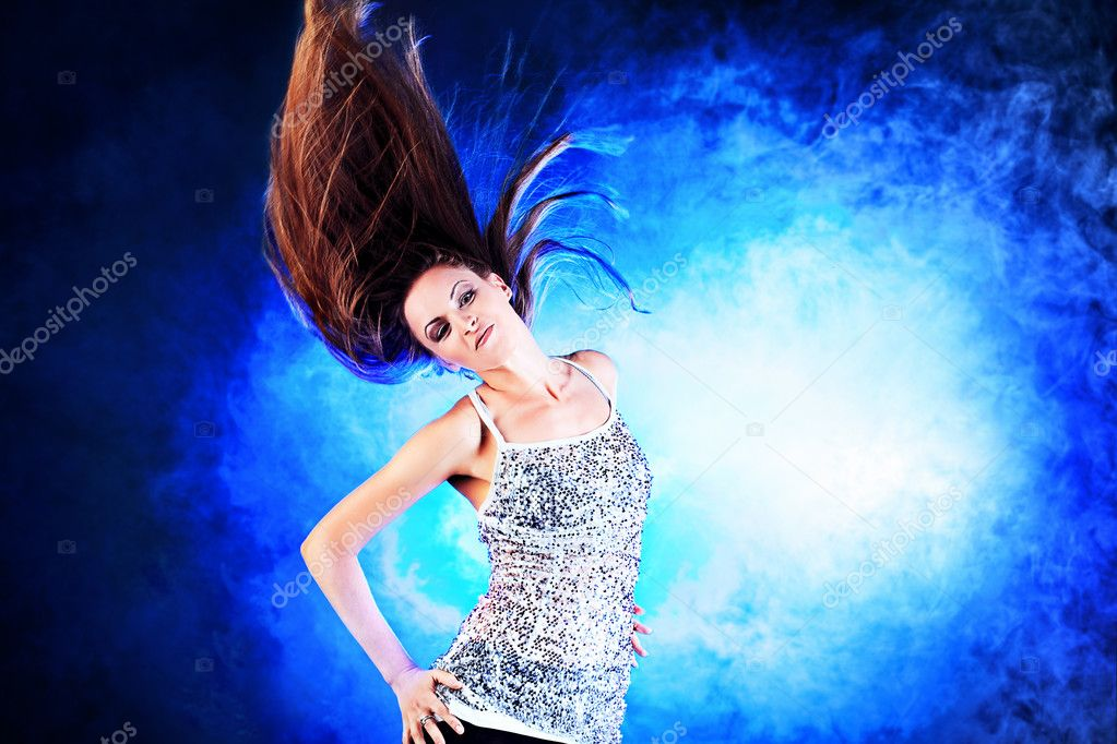 Beautiful girl dancing on disco in blue light and smoke.  Stock Photo #11794922