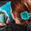 Woman on couch with blanket and cup of tea — Stock Photo