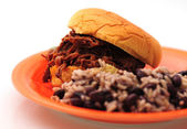 Shredded beef sandwich on an orange plate with beans and rice — Stock Photo