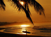 Susnet in tropical location with surfer — Stock Photo