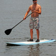 Man getting exercise by paddleboarding — Stock Photo #10899805