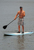 Man getting exercise by paddleboarding — Stock Photo