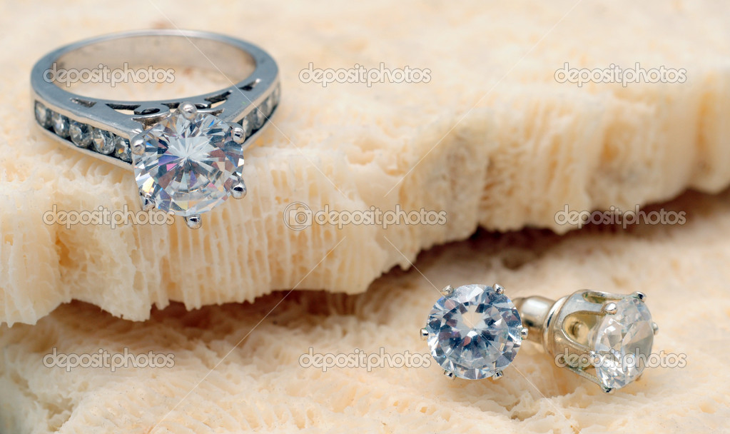 Beautiful diamond engagement ring and diamond stud earrings on coarl — Stock Photo #10909260