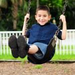 Happy young child swinging — Stock Photo