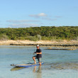Man on paddle board fishing - Foto Stock