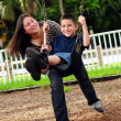 Mother pushing son on swing — Stock Photo