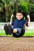 Happy young child swinging — Stockfoto