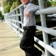 Cute Boy leanings against pole on bridge — Stock Photo