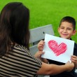 Stock Photo: Son giving mom heart drawing