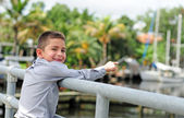 Very happy child pointing at boats — Stock Photo