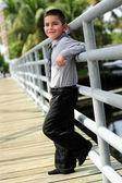 Cute Boy leanings against pole on bridge — Stock Photo