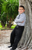 Serious Young boy leaning against tree — Stock Photo