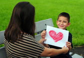 Son giving mom heart drawing — Stockfoto