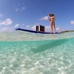 Beautiful woman fishing from paddle board — Stock Photo #11133385