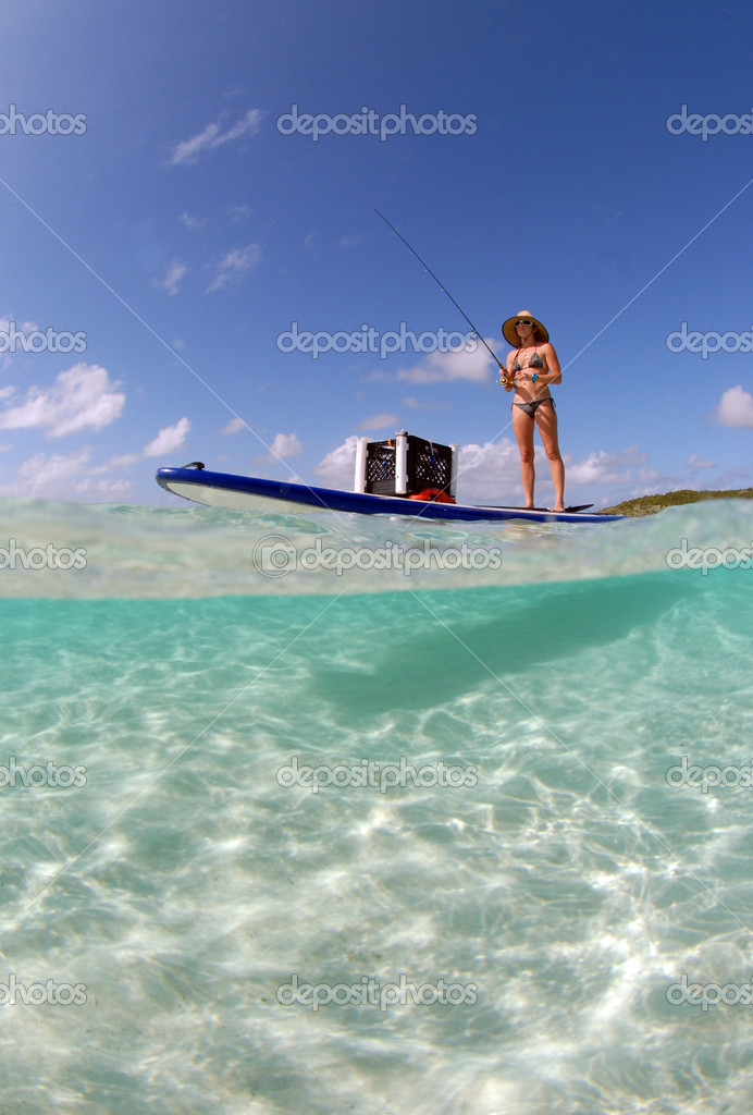 Beautiful woman fishing from paddle board stock photo for Fly fishing paddle board