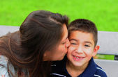 Mom kissing young son on cheek — Stockfoto