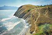Steep cliff at the edge of the sea, against the backdrop of the Crimean Mountains. — Stock Photo