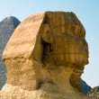 Stock Photo: Head of Sphinx in background of Cheops pyramid