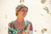 Portrait of a blonde in a sarafan on the background the sand dune — Stock Photo