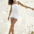 Brunette in white dress against a background of sand — Stock Photo