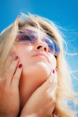 Portrait of a young woman wearing sunglasses, looking to the sky. — Stock Photo