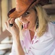 Royalty-Free Stock Photo: The girl in the cowboy hat fool around, showing the tongue.