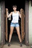 Meisje die zich voordeed bij de ingang van een sallon stijl wild west. — Stockfoto